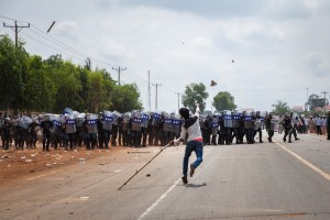 Demonstrators throw sticks and rocks to the police during the clash in front of Sabrina Factory. Workers have been on strike since May 25, 2013 demanding a salary increase.