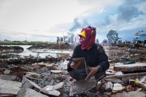 A woman finds a photo album under the rubble hours after eight houses in Village 22 were demolished by excavators during a forced eviction at Boeung Kak.