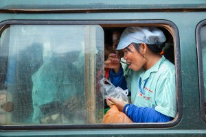 A woman eats while she waits for her minivan to take her home after her shift at a garment factory in Kampong Speu province, Cambodia.