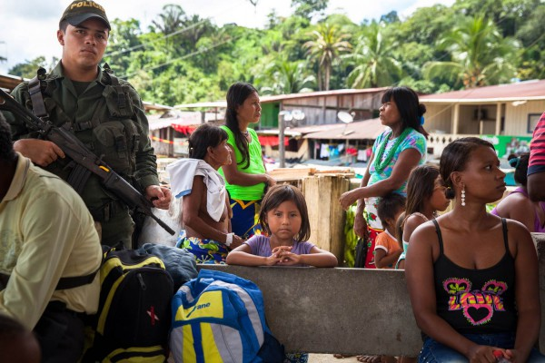 An Embera indigenous girl waits for transportation next to a policeman at Puerto Meluk in Bajo Baudó.