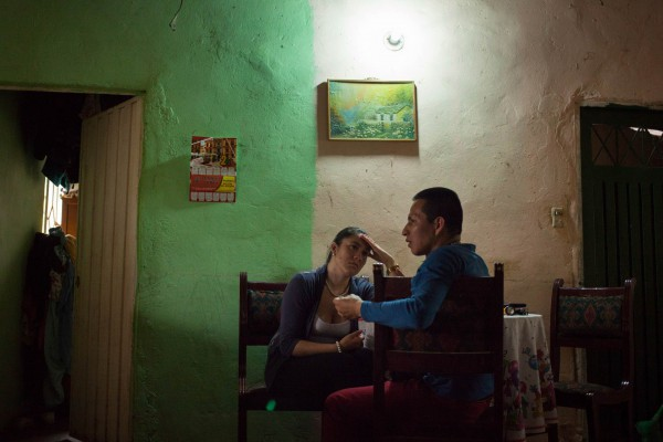 """Fabio, an ex-commander for the FARC, and his girlfriend Yisel talk after dinner during a visit to Camilo's house, a fellow demobilised from the ELN. """"I never had anything to do with the conflict in Colombia, until I met him. I've never had such a difficult relationship before, but I don't regret"""", says Yisel. """"I asked the ACR for psychological support, but they didn't provide anything""""."""