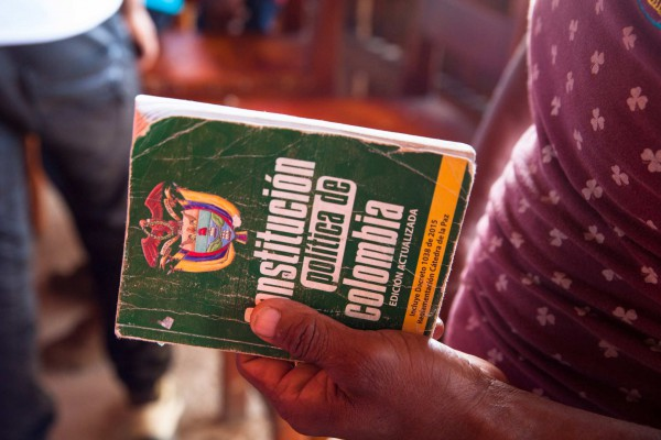 """A community leader holds a copy of Colombia's constitution during a meeting held by government officials about the crop-substitution programme to cocaleros from Tierralta's region. """"They think we're stupid, but we know the law. We have to come prepared to defend ourselves,"""" he said."""