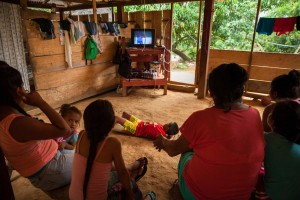 Women and children watch a soap opera at their home in Gallo.
